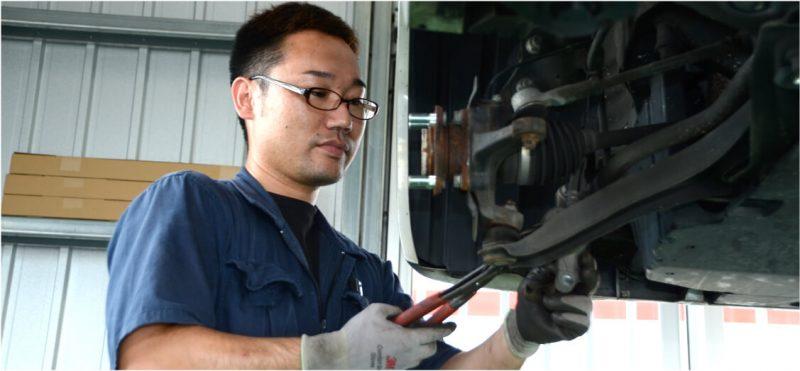 車検整備のため車の足回りを調整する整備士