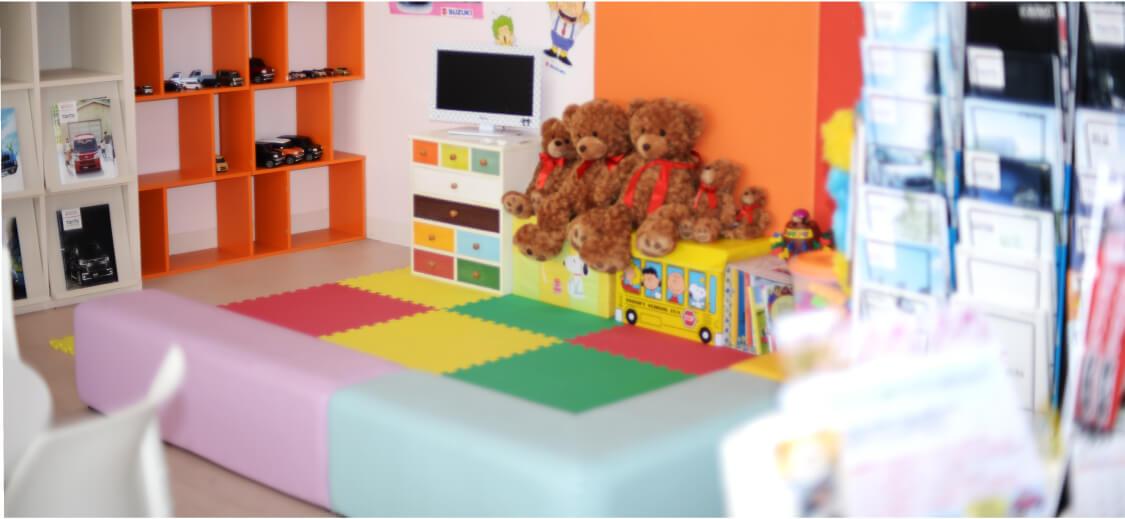 ウレタンの仕切りで囲まれたキッズルームの写真。床はウレタンクッションのパネルが張られていて、ぬいぐるみなどのおもちゃがあります。